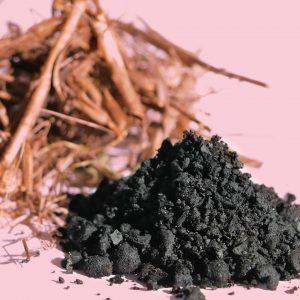 Kohlehäufchen, dahinter getrocknete Pflanzenschnitzel