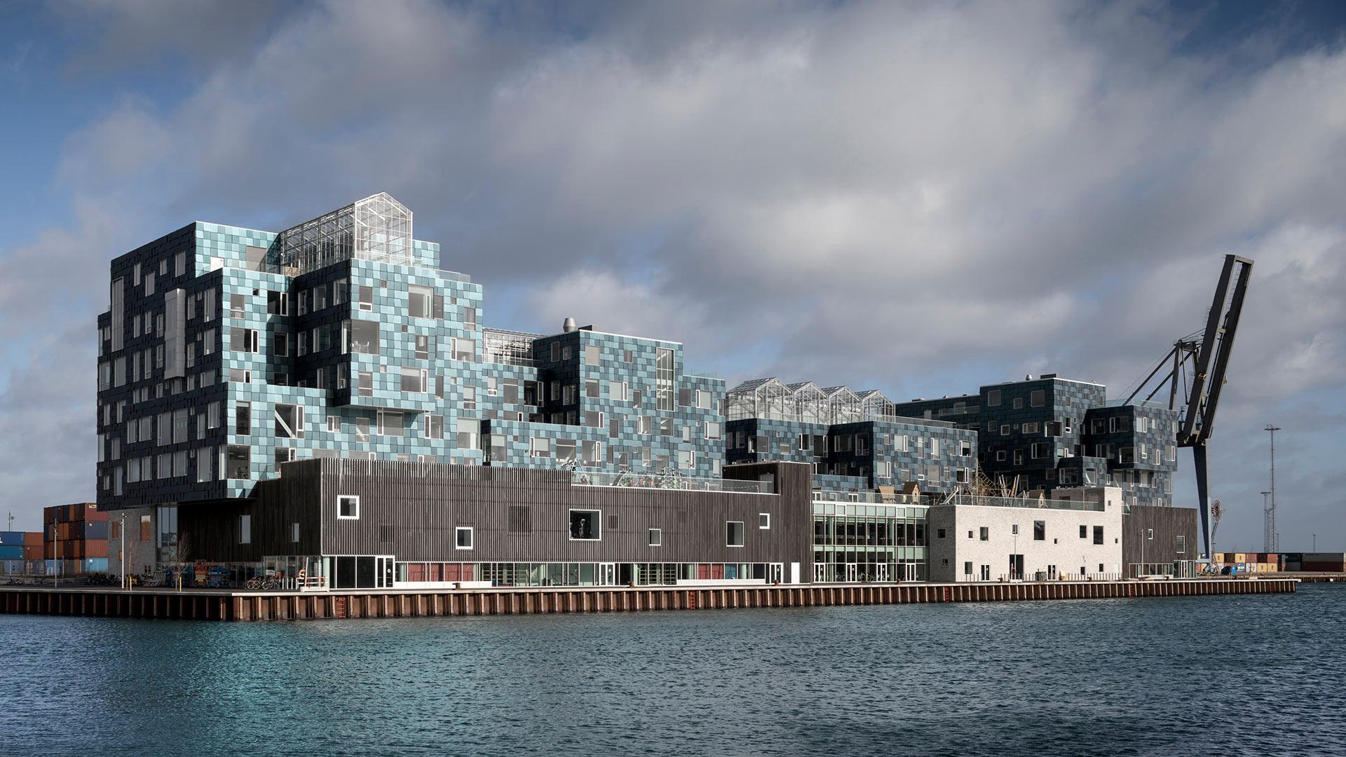 Hochmodernes, oben türkisfarbenes Gebäude an einem Hafenbecken
