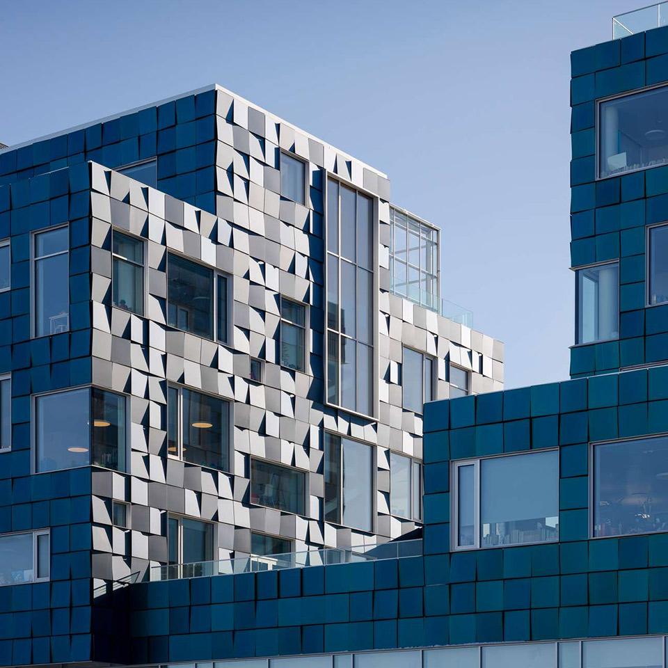 Fassade aus Quadraten in Türkis-Schattierungen, die sich in verschiedene Richtungen von der Ebene abheben
