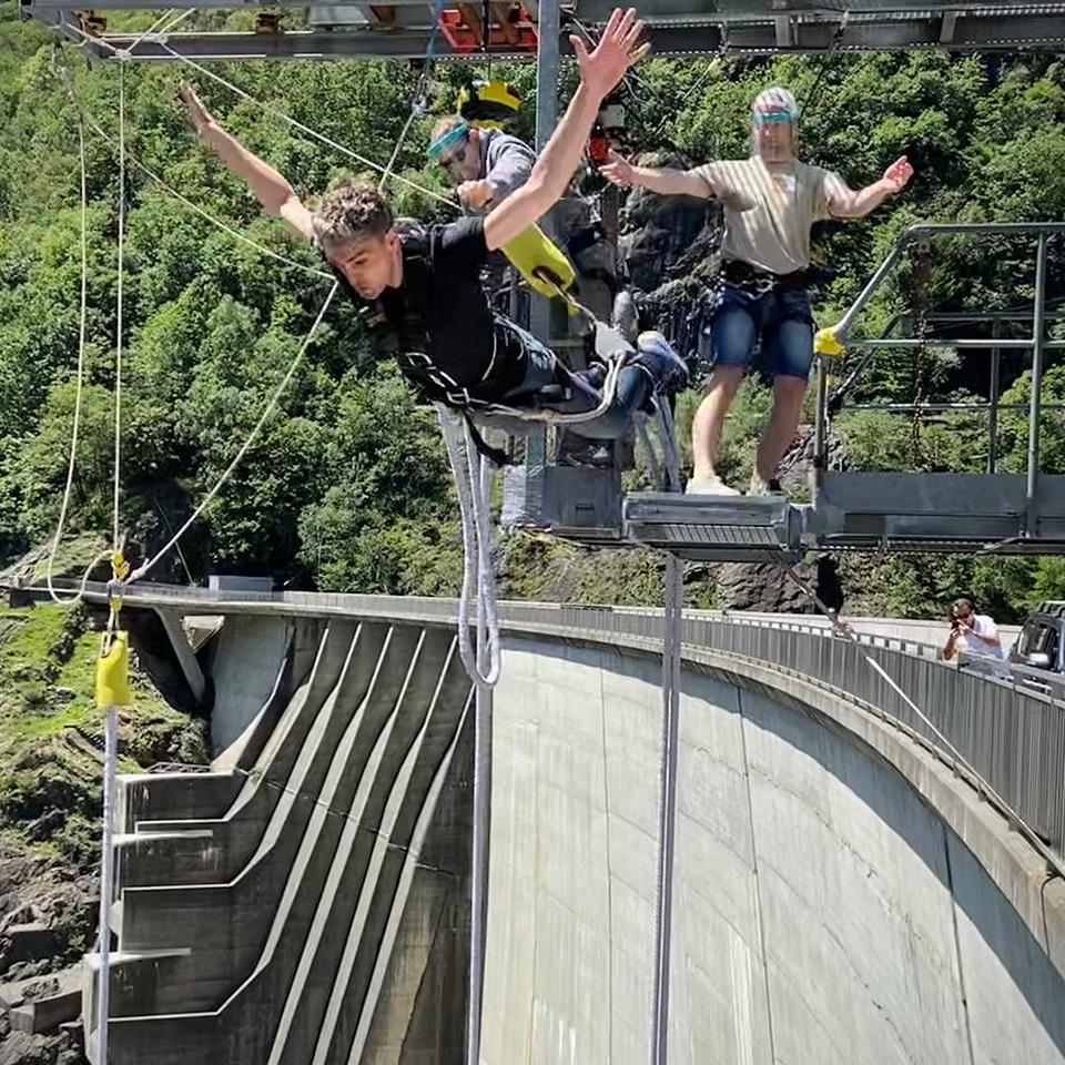 Mann springt von einer Plattform an der Staumauer in die Tiefe