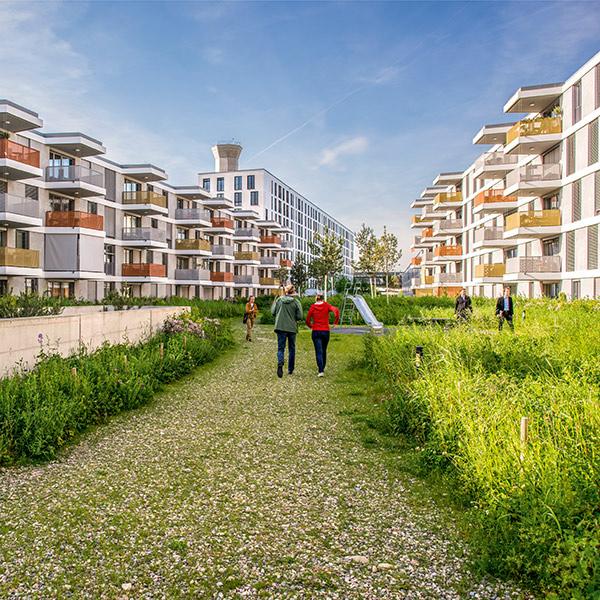 Weg im Grünen zwischen modernen Wohnbauten mit vorstehenden Balkonen