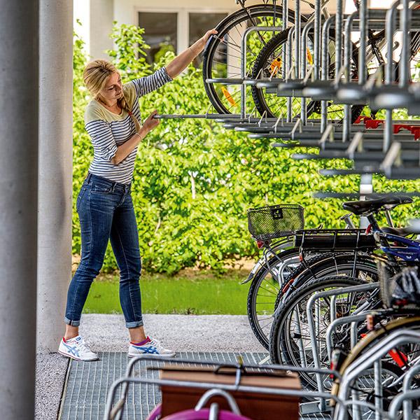 Doppelstöckige, gedeckte Fahrradstation; junge Frau holt Velo aus der oberen Etage