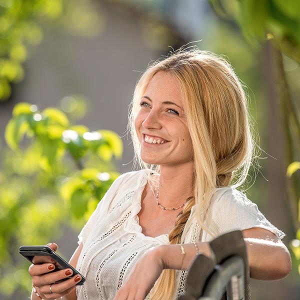 Frau mit Smartphone auf Parkbank