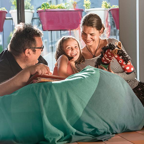Junge Familie beim gemeinsamen Lesen vor hellem grossem Fenster