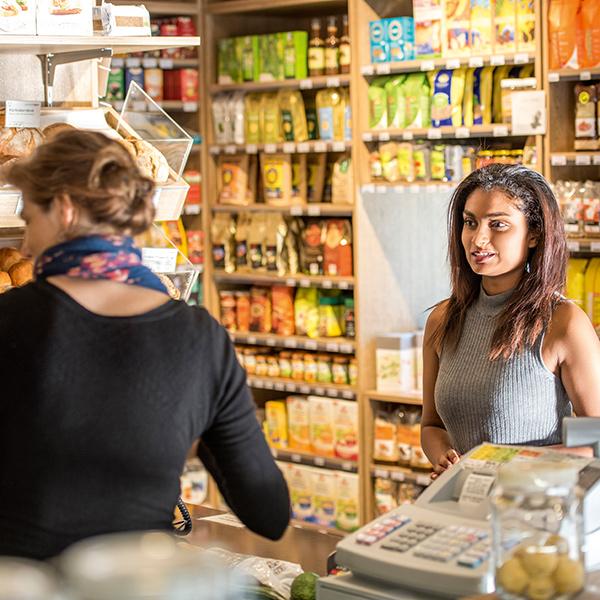 Junge Frau beim Einkauf im Quartierladen