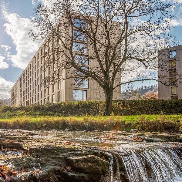 Wasser fliesst über eine Stufe, im Hintergrund moderne Wohnblöcke