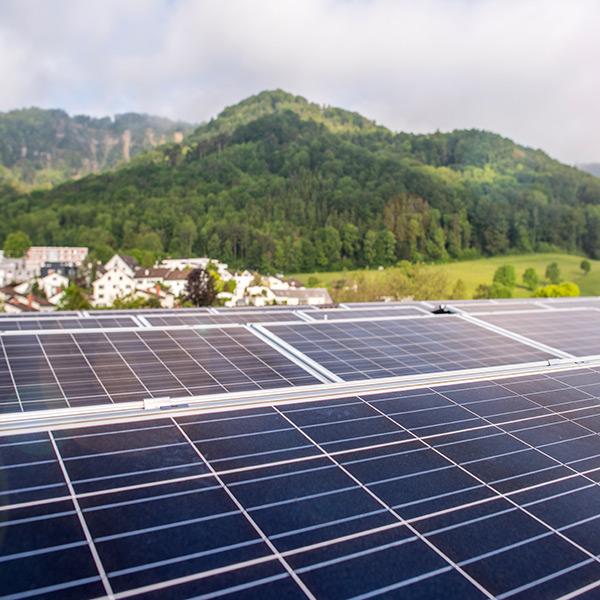 Solarpanels auf dem Dach, im Hintergrund Wohnhäuser und bewaldete Hänge