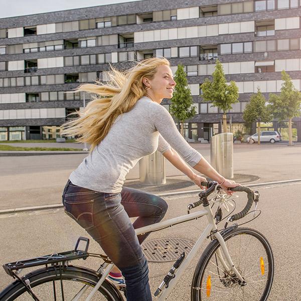 Frau mit wehendem blondem Haar auf Rennrad