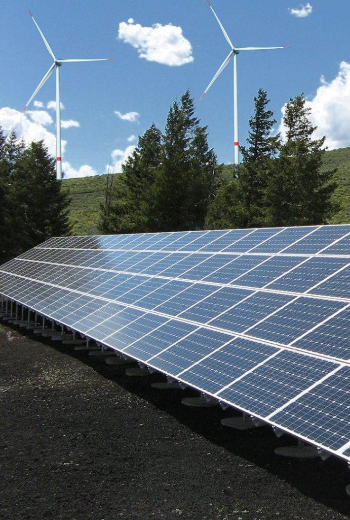 Solarkraftwerk, Windturbinen auf Hügel im Hintergrund