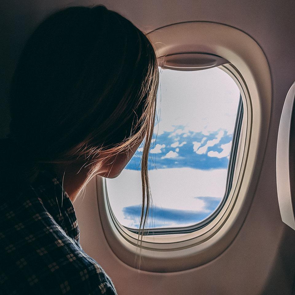 Frau blickt aus Flugzeugfenster